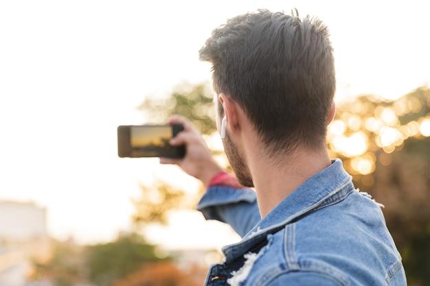 Hübscher junger mann, der draußen geht und selfie per handy nimmt