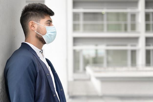 Hübscher junger mann, der draußen im medizinischen masken-coronavirus-konzept steht
