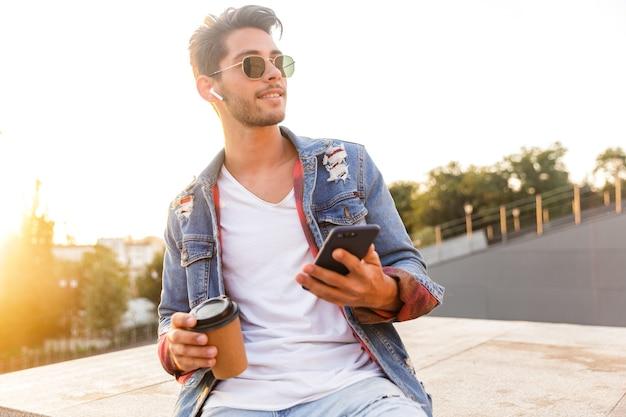 Hübscher junger mann, der draußen mit dem handy geht, kaffee trinkt und musik hört