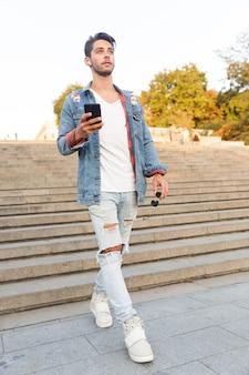 Hübscher junger mann, der draußen mit dem handy geht und musik hört