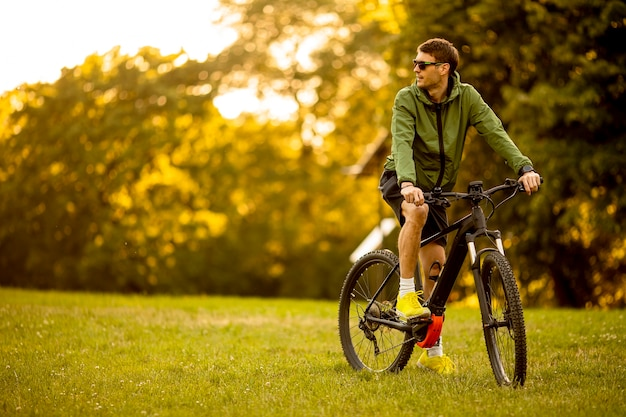 Hübscher junger mann, der e-bike im park reitet