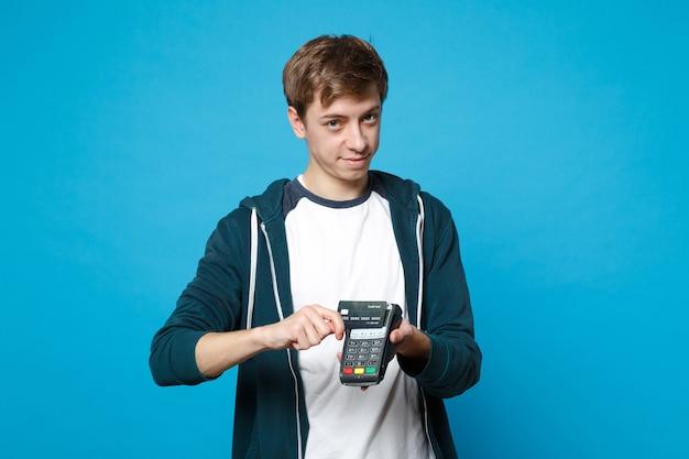 Hübscher junger mann, der ein drahtloses modernes bankzahlungsterminal hält, um kreditkartenzahlungen einzeln auf blauer wand zu verarbeiten und zu erwerben. menschen aufrichtige emotionen, lifestyle-konzept.