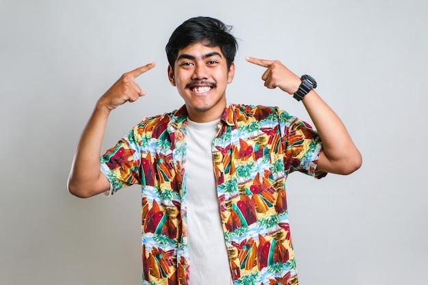 Hübscher junger mann, der ein lässiges hemd trägt und mit beiden händen auf den kopf zeigt, finger, tolle idee oder gedanke, gutes gedächtnis auf weißem hintergrund
