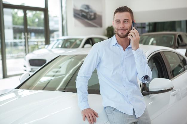 Hübscher junger mann, der ein neues auto am verkaufsstellensalon kauft