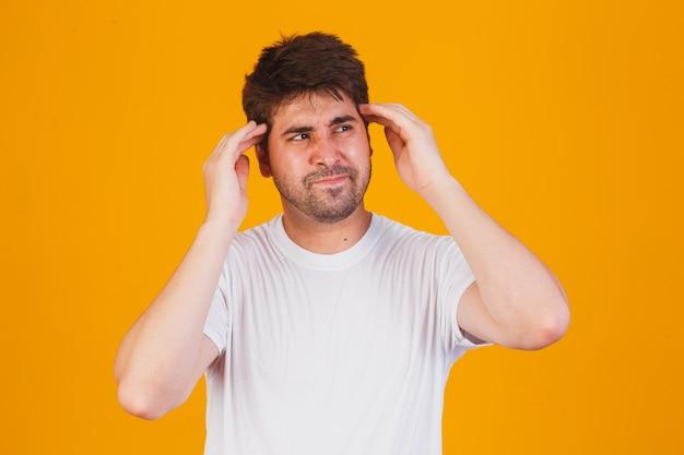 Hübscher junger mann, der ein weißes t-shirt mit seiner hand auf seinem kopf für kopfschmerzen wegen des stresses trägt