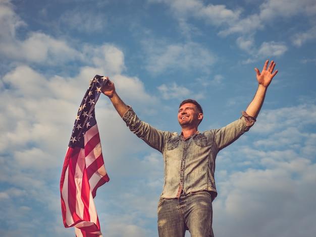 Hübscher, junger mann, der eine amerikanische flagge hält