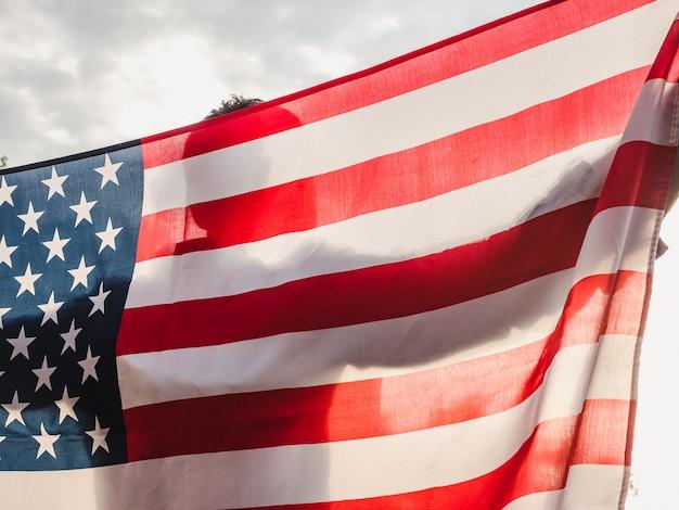 Hübscher, junger mann, der eine amerikanische flagge wellenartig bewegt