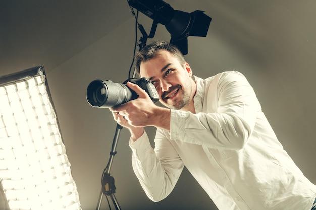Hübscher junger mann, der eine dslr-kamera hält.
