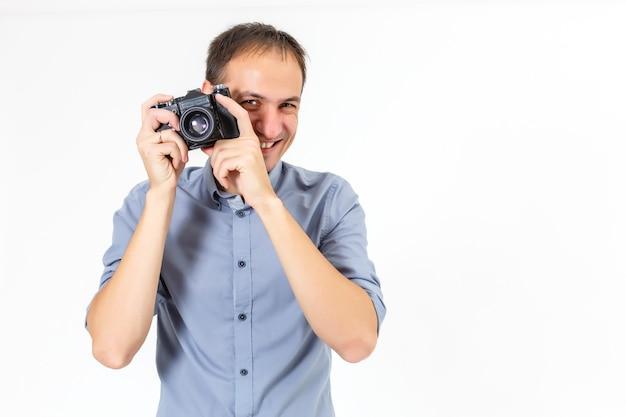 Hübscher junger mann, der eine kamera hält. auf weiß.