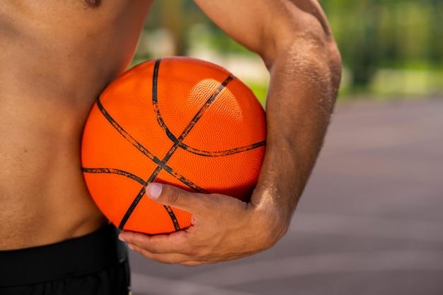 Hübscher junger mann, der einen basketball hält