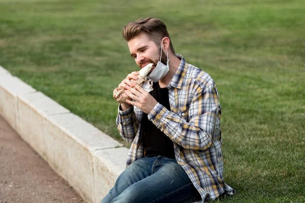 Hübscher junger mann, der einen kebab isst