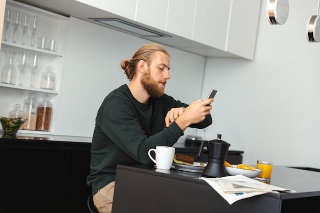 Hübscher junger mann, der frühstückt, zeitung liest, während er an der küche sitzt