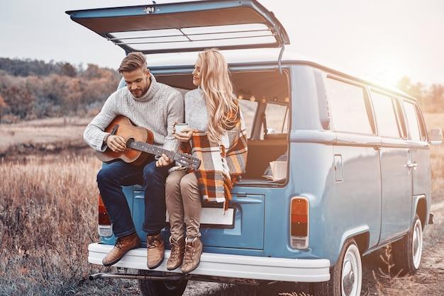 Hübscher junger mann, der gitarre für seine freundin spielt, während beide draußen im kofferraum sitzen