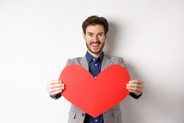 Hübscher junger mann, der glücklichen valentinstag wünscht, großes rotes herzzeichen gibt und lächelt, überraschung zum liebhaber macht, im anzug über weißem hintergrund stehend.