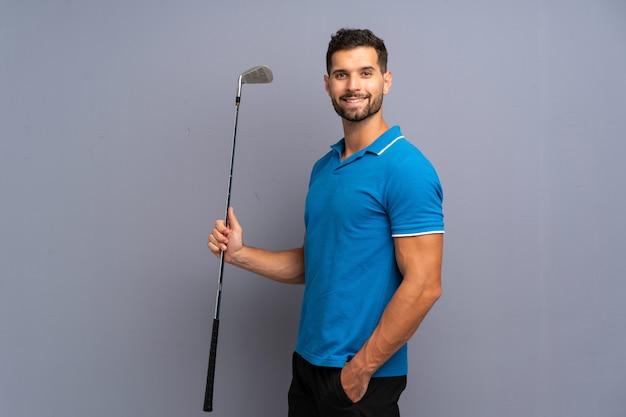 Hübscher junger mann, der golf spielt