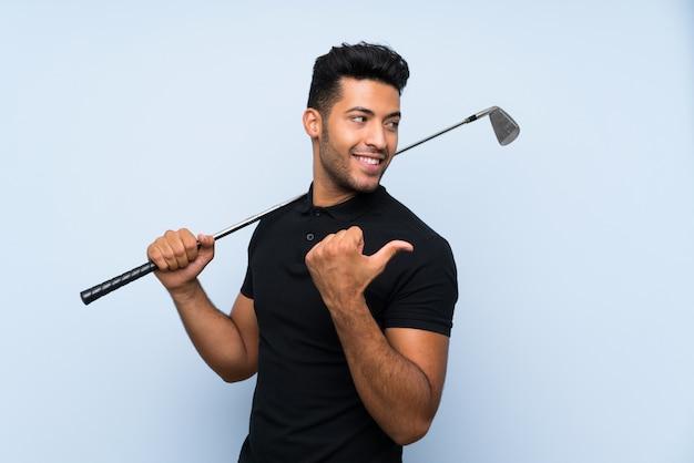 Hübscher junger mann, der golf über der lokalisierten blauen wand zeigt auf die seite spielt, um ein produkt darzustellen
