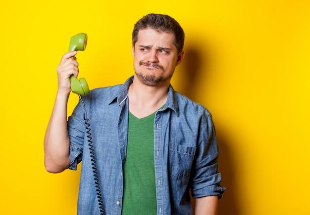 Hübscher junger mann, der grünes retro- telefon auf dem wunderbaren gelben hintergrund hält