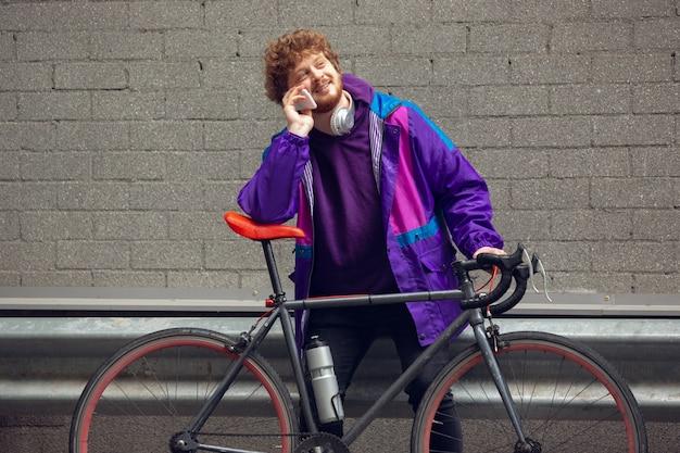 Hübscher junger mann, der handy und kopfhörer benutzt, während er neben seinem fahrrad neben ihm steht