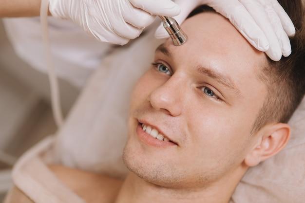 Hübscher junger mann, der hautpflegebehandlung im schönheitssalon erhält