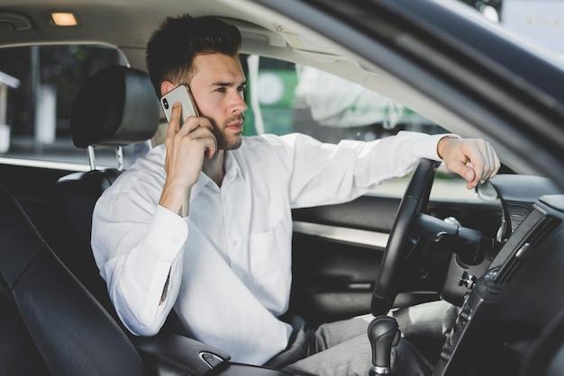 Hübscher junger mann, der im auto spricht am handy sitzt
