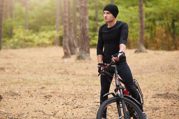 Hübscher junger mann, der im ländlichen wald radelt, attraktiver sportlicher kerl, der schwarzen trainingsanzug trägt, der fahrrad unter freiem himmel reitet, männlich stoppt, um ruhe zu haben und genießt schöne natur.