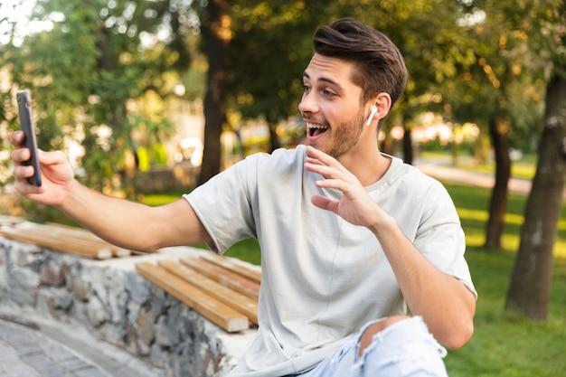 Hübscher junger mann, der im park draußen sitzt und ein selfie per handy nimmt und musik mit kopfhörern hört
