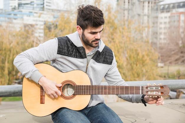 Hübscher junger mann, der im park spielt gitarre sitzt
