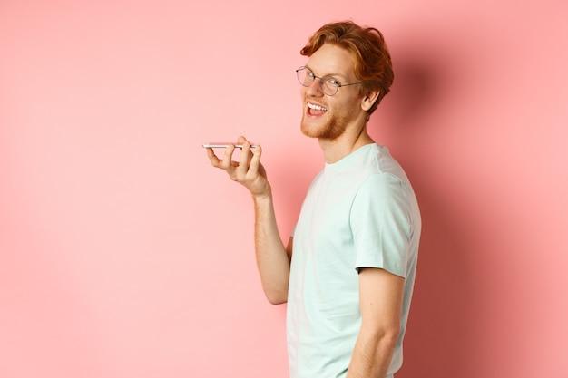 Hübscher junger mann, der im profil steht und auf lautsprechern spricht, sprachnachricht aufzeichnet, kopf an kamera dreht und erfreut lächelt, über rosa hintergrund stehend.