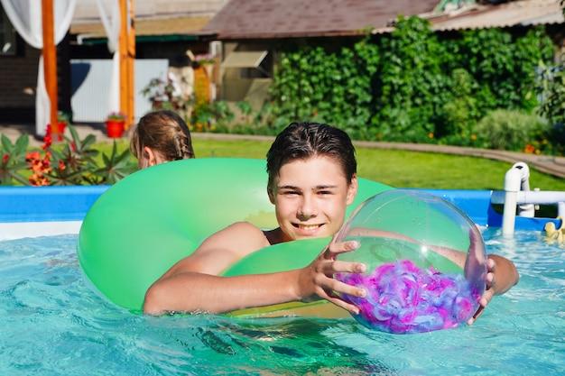 Hübscher junger mann, der im sommer in einem schwimmbad mit einem ball im hinterhof lächelt und lacht