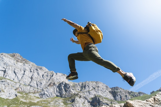 Hübscher junger mann, der in den berg springt.