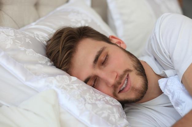 Hübscher junger mann, der in weißer bettwäsche schläft.