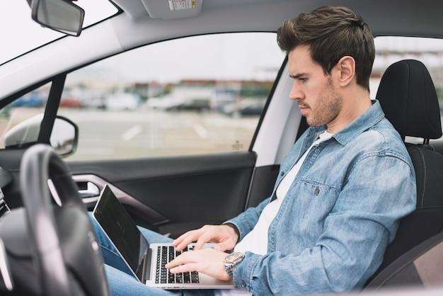 Hübscher junger mann, der innerhalb des autos unter verwendung des laptops sitzt