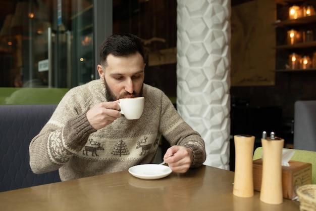 Hübscher junger mann, der kaffee am kaffeehaus trinkt