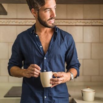 Hübscher junger mann, der kaffeetasse in seiner hand hält