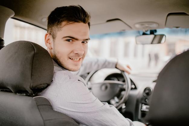 Hübscher junger mann, der kamera betrachtet, die in einem auto sitzt, blick vom rücksitz