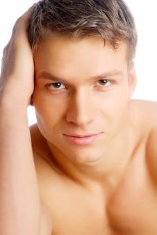 Hübscher junger mann, der kamera betrachtet. nackter oberkörper.