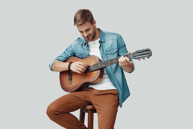 Hübscher junger mann, der lächelt und gitarre spielt, während er vor grauem hintergrund sitzt