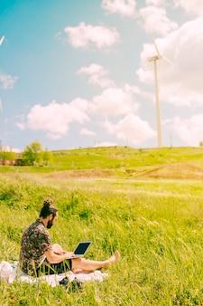 Hübscher junger mann, der laptop in der landschaft hält