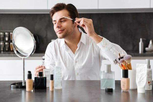 Hübscher junger mann, der make-up und schönheitsprodukte aufträgt