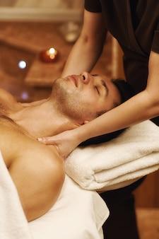 Hübscher junger mann, der massage am spa-zentrum genießt