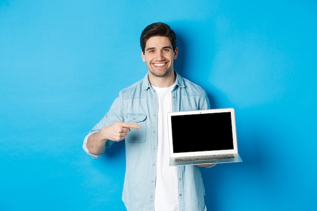 Hübscher junger mann, der mit dem finger auf den bildschirm des computers zeigt, erfreut lächelt, promo im internet oder auf der website zeigt, auf blauem hintergrund stehend.