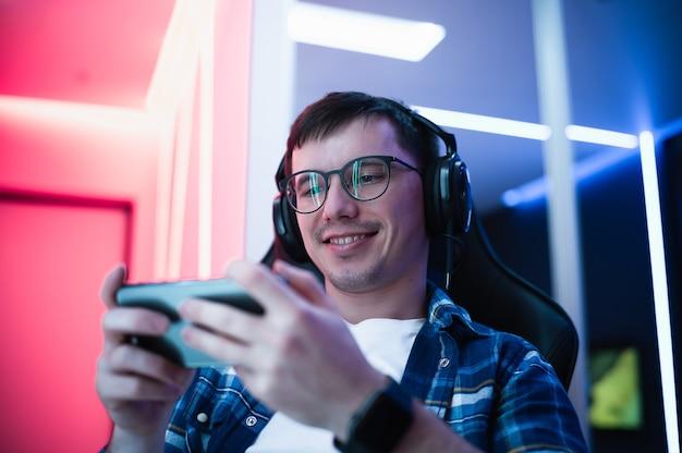 Hübscher junger mann, der mit seinem smartphone im neonfarbraum spielt.