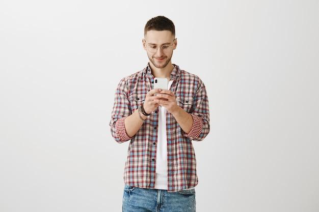 Hübscher junger mann, der mit seinem telefon aufwirft
