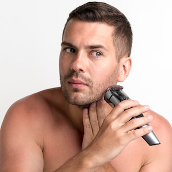 Hübscher junger mann, der mit trimmer auf weißem hintergrund sich rasiert