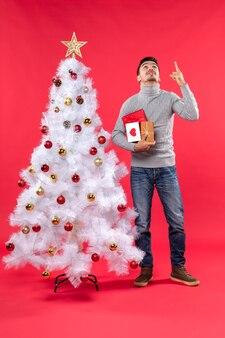Hübscher junger mann, der nahe dem verzierten weißen neujahrsbaum steht