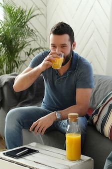 Hübscher junger mann, der orangensaft zu hause trinkt