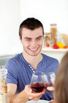 Hübscher junger mann, der restaurant mit seinem trinkenden gewinn der freundin trinkt