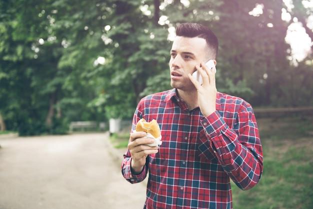 Hübscher junger mann, der sandwich-autotür isst. er hält ein telefon in der hand