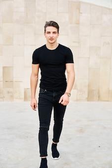 Hübscher junger mann, der schwarze kleidung trägt