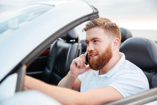 Hübscher junger mann, der sein auto fährt und auf dem handy spricht